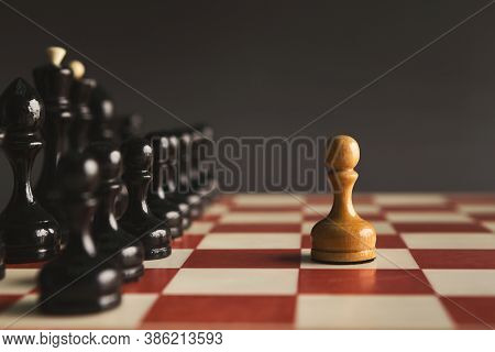 One Pawn Standing Against Set Of Black Chess. Alone Against Many Enemies, Symbol Of Difficult Fight