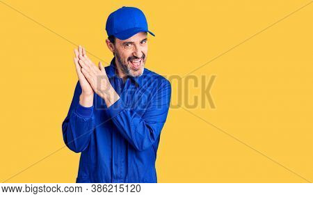 Middle age handsome man wearing mechanic uniform clapping and applauding happy and joyful, smiling proud hands together