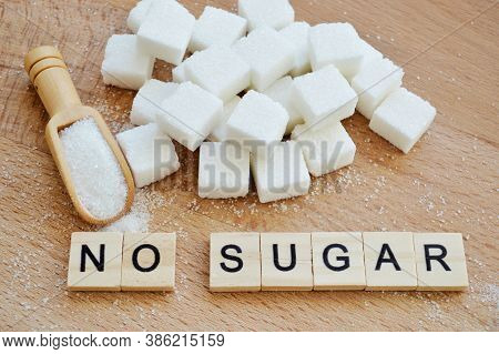 Refined Sugar And Wooden Spoon With Loose Sugar On Wooden Background. Word No Sugar Of Wooden Blocks
