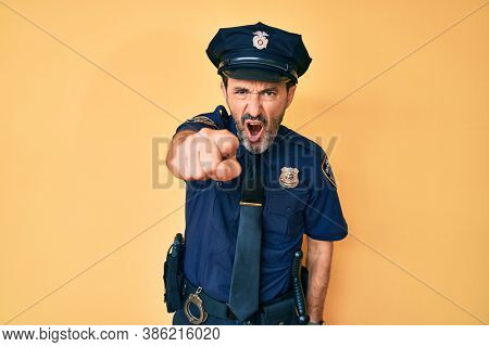 Middle age hispanic man wearing police uniform pointing displeased and frustrated to the camera, angry and furious with you