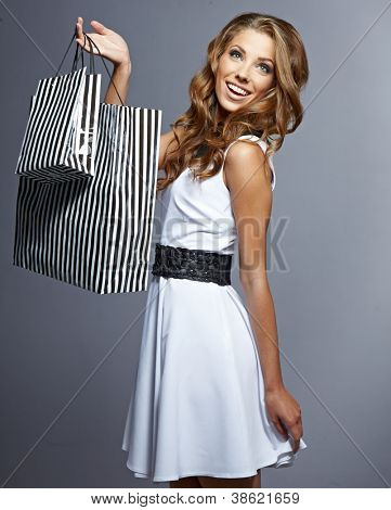 Woman holding shopping bags against a grey background