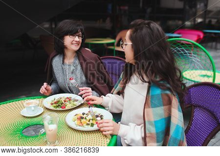 Mature Mother And Her Young Daughter Sit Together In Cafe Or Restaurant. Cheerful Family With Good S