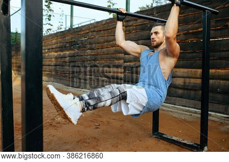 Muscular man doing abs exercise, street workout