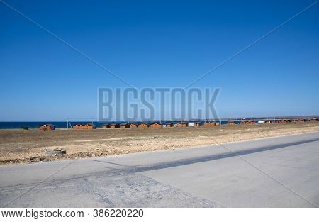 Bright Orange Bungalows Stand In The Steppe Next To The Sea. A Sunny Summer Day With A Cloudless Sky