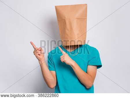 Teen boy with paper bag over head pointing finger away at copyspace, on gray background. Teenager cover head with shopping bag pointing finger at something. Child pulling paper bag over head