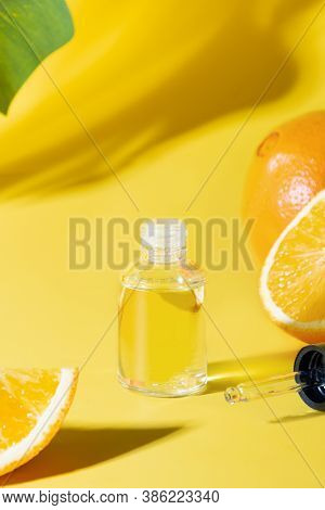 Cosmetic Oil, Hyaluronic Acid Or Essence On Yellow Background. Anti-age Care. Close Up. Vertical For