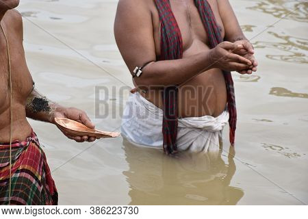 Tarpan Is Being Performed By Indian Hindu Devotees On The Banks Of The Holy River Ganga In Kolkata,