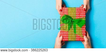 Top View Of A Man And A Woman Holding A Gift On Colorful Background. Concept Of Giving And Receiving