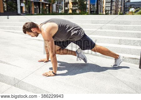 Young Man Exercising Outside. Athletist Doing Mountain Climber Training. Exercising Alone In Horizon