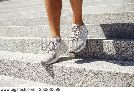 Young Man Exercising Outside. Picture Of Mans Feet In Sneakers Walking Down Steps Outside Duing Suns