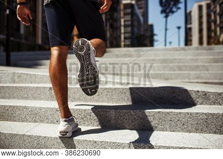 Young Man Exercising Outside. Back Low View Of Strong Males Legs, Calfs And Feet In Sneakers. Athlet