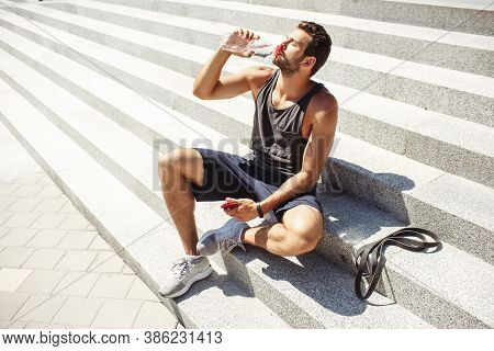 Young Man Exercising Outside. Athlete Sit On Steps Outside And Thursting. Drinking Water And Enjoy I