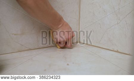 The Master Is Rubbing The Seam Between The Tiles. Master Tiler Glues Wall White Ceramic Tiles. Maste