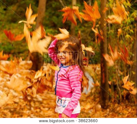 Photo of little cute girl playing in autumn park, adorable sweet kid throwing up old dry foliage, cheerful small female child playing outdoors, nice toddler laughing with closed eyes