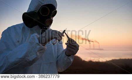 Ecologist Holding Tweezers And Glass Tube With Sample Of Raw Material For Laboratory Test. Research