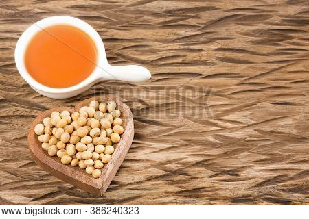 Soy Bean And Soy Oil On Wooden Table - Glycine Max. Text Space