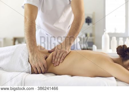 Male Osteopath Massages The Back Of A Girl Lying On A Couch In A Bright Office.