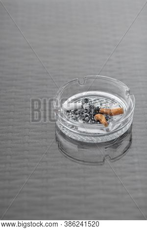 Close-up Of An Ashtray With Cigarette Butts. Glass Cigarette Ashtray On The Table. Three Filter Ciga