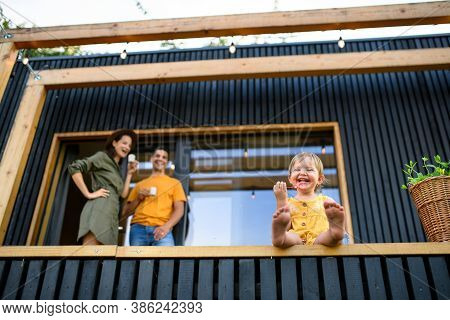 Low-angle View Of Family With Small Daughter Outdoors, Weekend Away In Container House In Countrysid