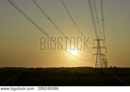 Power Lines Leading To Pylons Silhouette Against Sunrise At Dawn On Agricultural Land In Hoggeston,