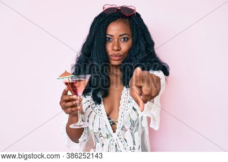 Beautiful african woman wearing summer look and drinking cocktail pointing with finger to the camera and to you, confident gesture looking serious