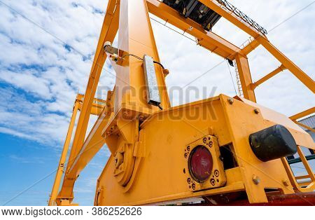 Bottom View Of Yellow Gantry Crane Against Blue Sky At Port. Gantry Crane For Cargo And Construction