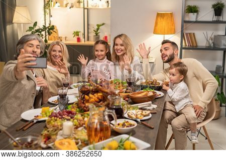 Happy large family of three generations waving hands while sitting by festive table, having Thnksgiving dinner and looking in smartphone