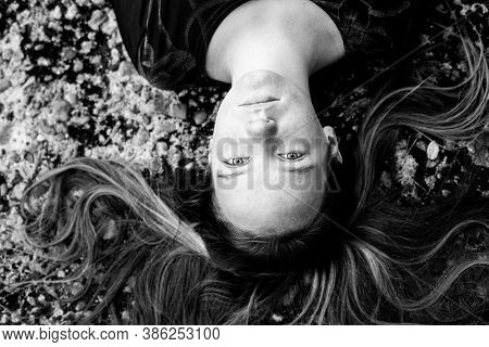Girl lying on the pavement with her long hair, top view. Black and white photography.