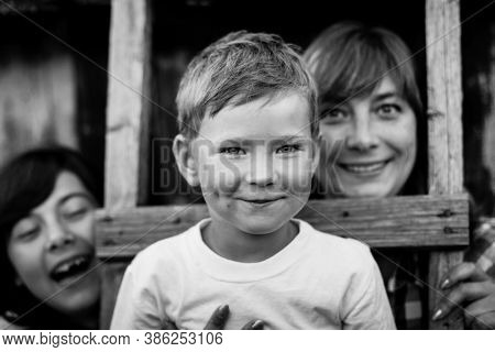 Little boy with his mother and older sister. Black and white photography.
