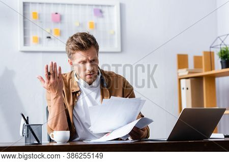 Discouraged Businessman With Wireless Headphones On Neck Working With Papers In Office