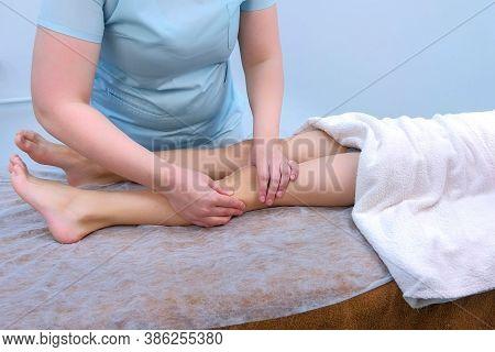 Doctor Masseur Massagist Making Therapeutic Massage To Teen Boy On Legs In Clinic, Closeup Legs. Dys