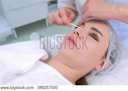 Cosmetologist Wiping Solution From Girls Lashes Using Cotton Stick On Lift Lamination Procedure In C