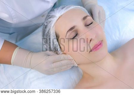 Cosmetologist In Gloves Cleans Wipes Mature Womans Face With Cotton Pads In Beauty Clinic, Face Clos
