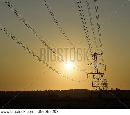 National Grid Electricity Power Supply Lines Leading To Pylons Fading To The Horizon Across Agricult