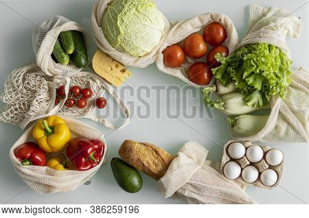 Womans Hand, Holding A Reusable Grocery Bag With Vegetables On A Kitchen At Home And Takes Cabbage O
