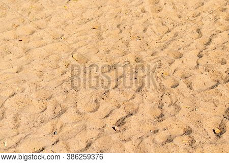 Sand Surface With Many Footprints And Footwear Of People On The Beach. Crossed Footprints After Walk