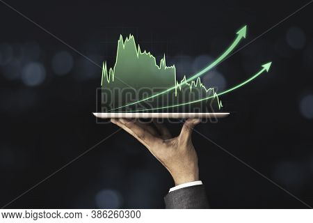 Businessman Holding Mobile & Tablet Which Showing Green Technical Stock Investment Graph With Increa