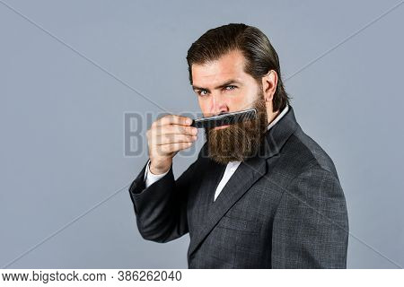 Master Grooming Hair And Beard In The Barbershop. Hairdresser Makes Hairstyle. Fashion Portrait Of H
