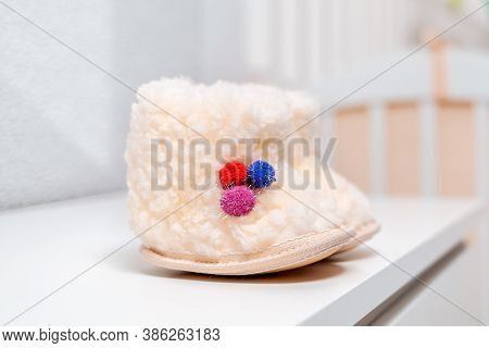 A Pair Of White Wool Baby Booties Are On The Dresser. Close Up. Nobody