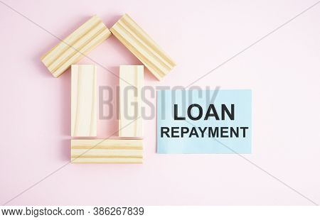 Home Loan Concept With Wooden House Model With Pink Background. Investment In Real Estate. Business
