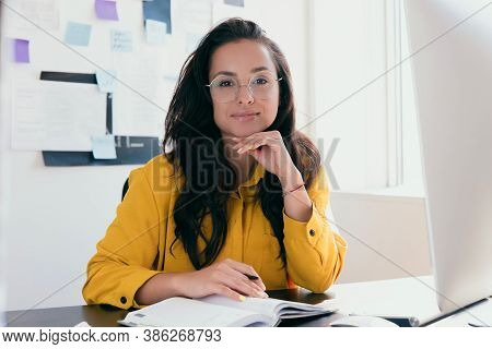 Successful Young Businesswoman Working From Home Or In Office. Woman With Long Brown Hair Wear Brigh