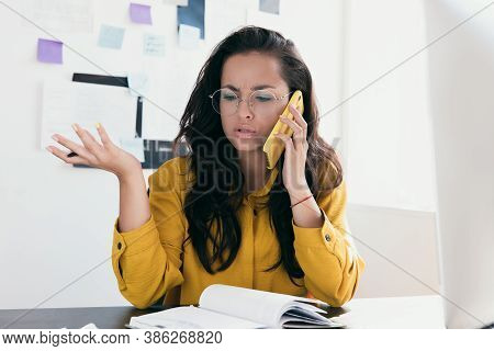 Upset Young Woman Sit At Office Desk Talking Over Phone Disappointed Hear Bad News. Caucasian Busine