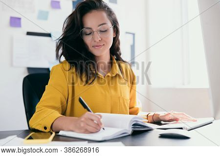 Concentrated Attractive Woman Siting At Office Desk And Writing Plans In Her Notebook. Smart White W