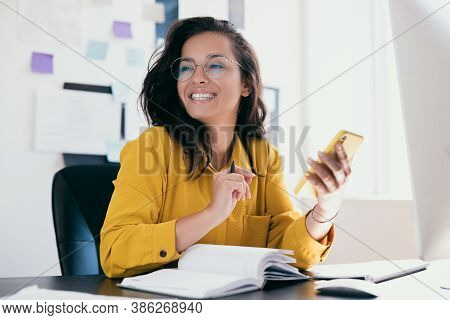 Pretty Cheerful Businesswoman Looking Away Sitting At Desk And Holding Phone In Hand. Positive Think