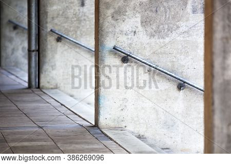 Concrete Walls With Cleaned Graffiti And A Rain Pipe Near Three Staircases With Railing