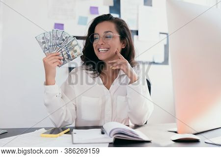Pleased Woman Wearing Office Clothing White Shirt And Round Glasses Holding Fan Of Money And Sitting