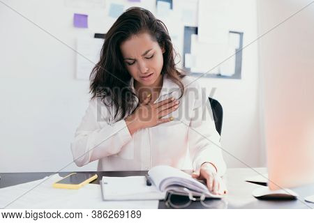 Beautiful Woman Sick With Feeling Pain In The Chest While Working With Papers. Hand Holding Chest Af