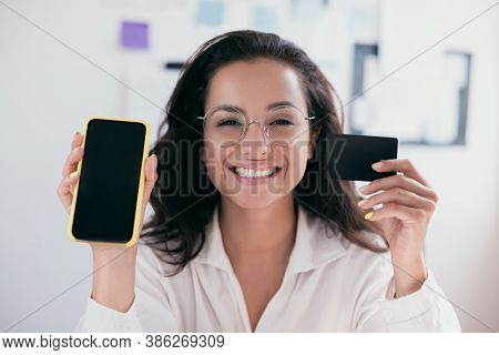 Causasian Cheerful Young Woman With Brown Hair Holding A Card And Smartphone, Smiling And Looking At