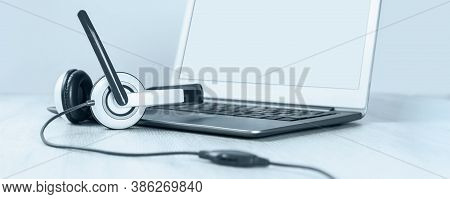 Laptop With Blank Screen And Headphones On White Desk Blue Background Banner. Distant Learning Or Wo