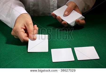 Cards in hands on green table